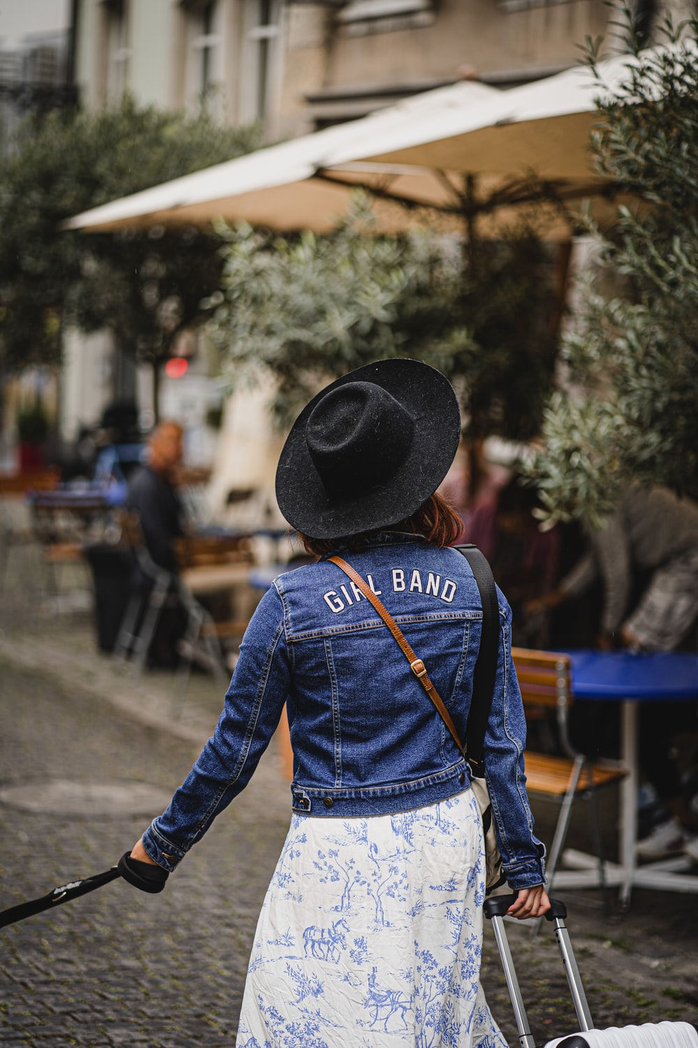 woman in blue denim jacket and white shirt wearing black hat standing on street during daytime
