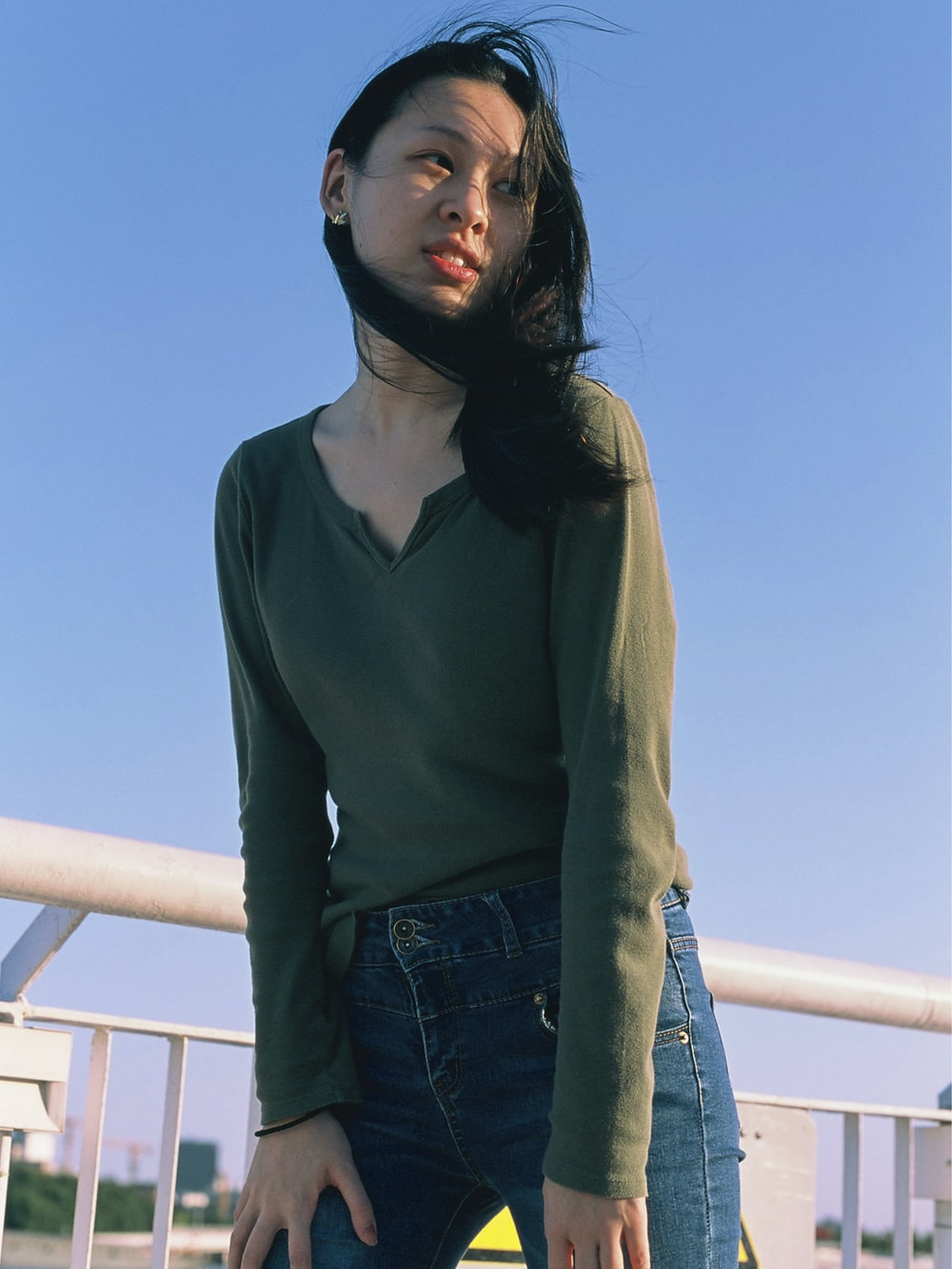 woman in green long sleeve shirt and blue denim jeans standing on white metal railings during