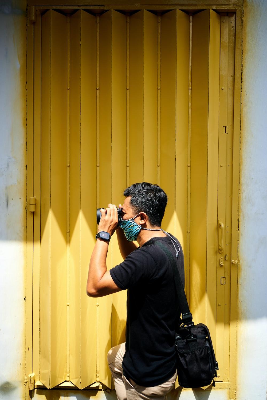 man in black long sleeve shirt taking photo of yellow wooden door