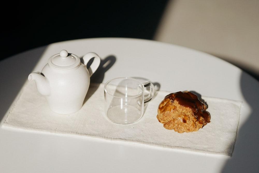 white ceramic teapot beside clear glass mug on white table