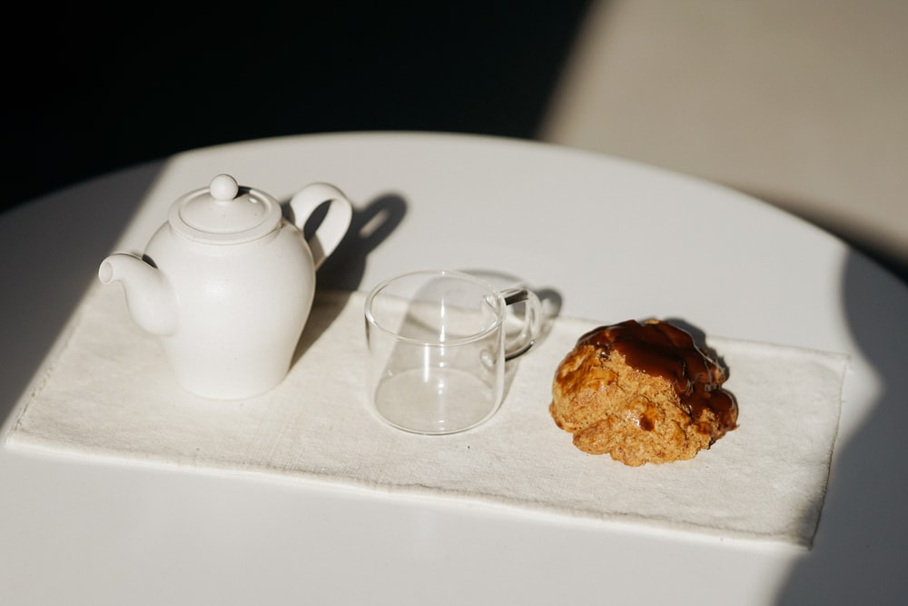 white ceramic teapot beside clear glass mug on white table