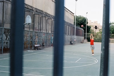 man in orange shirt and black shorts walking on basketball court during daytime basketball court teams background