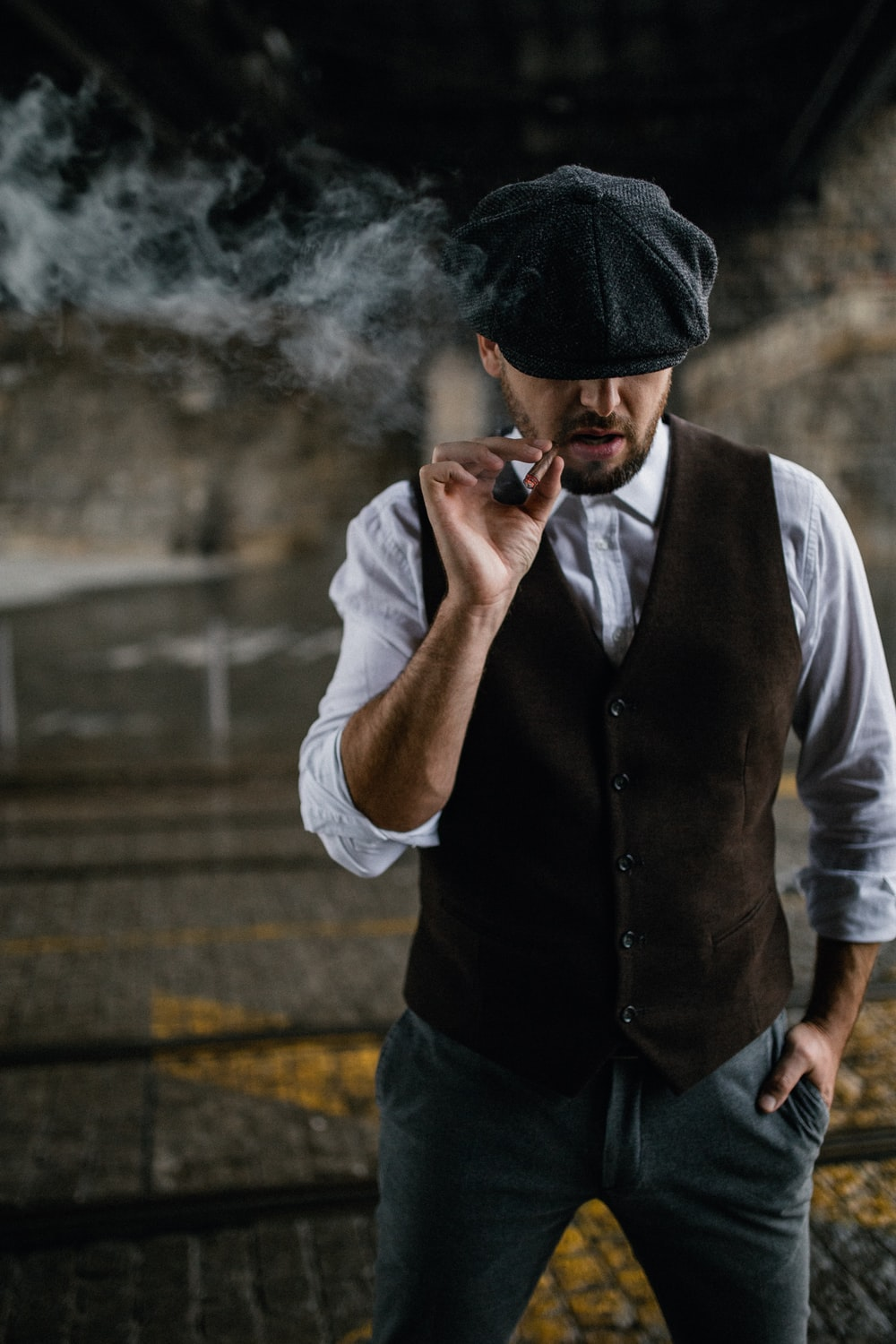 man in black vest and white dress shirt smoking cigarette