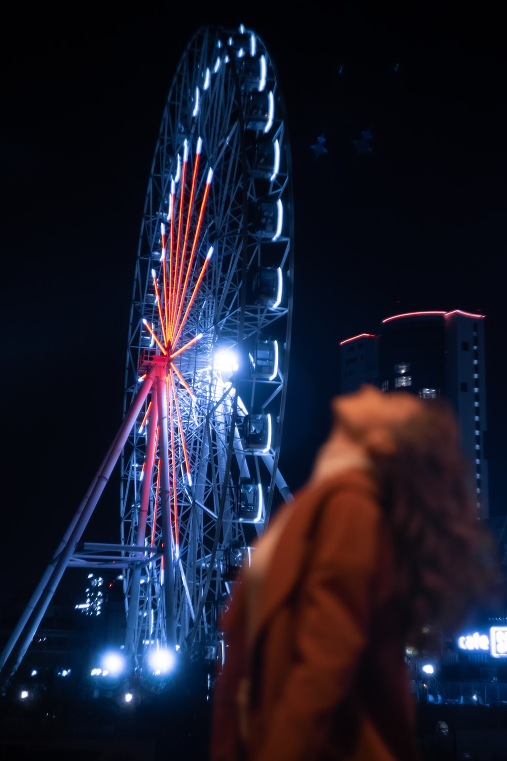 woman in yellow jacket standing near ferris wheel during night time