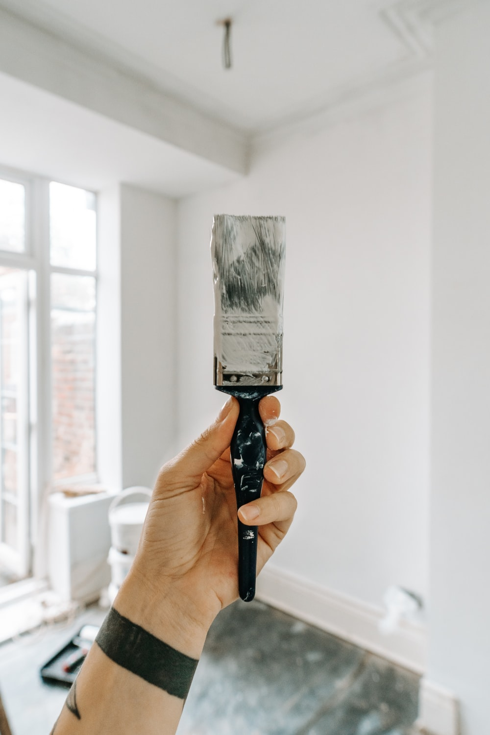 person holding white paint brush