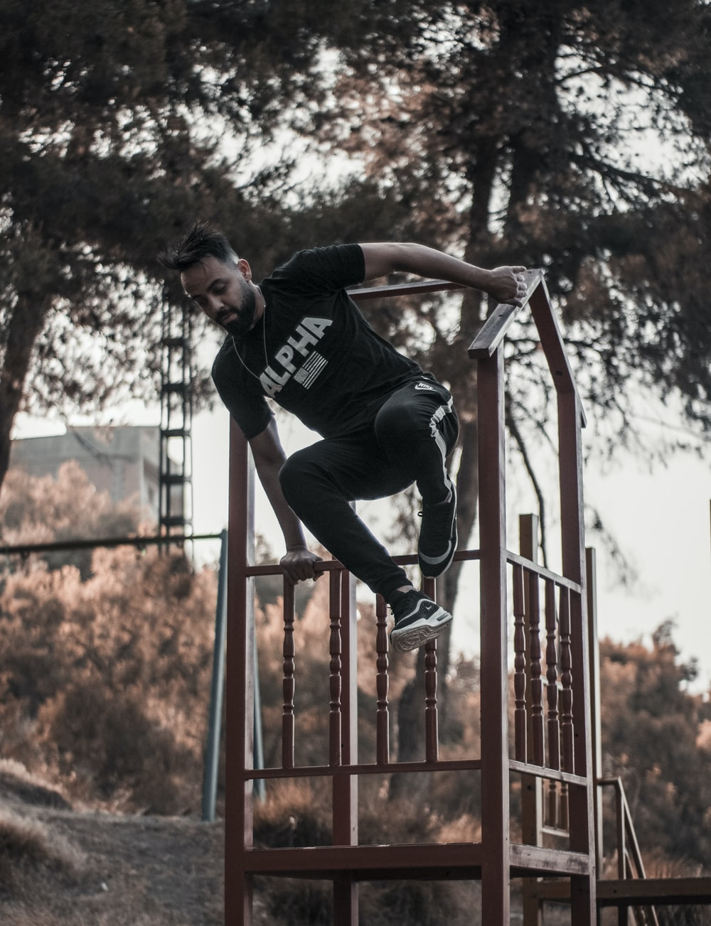 man in black t-shirt and black pants jumping on red metal railings
