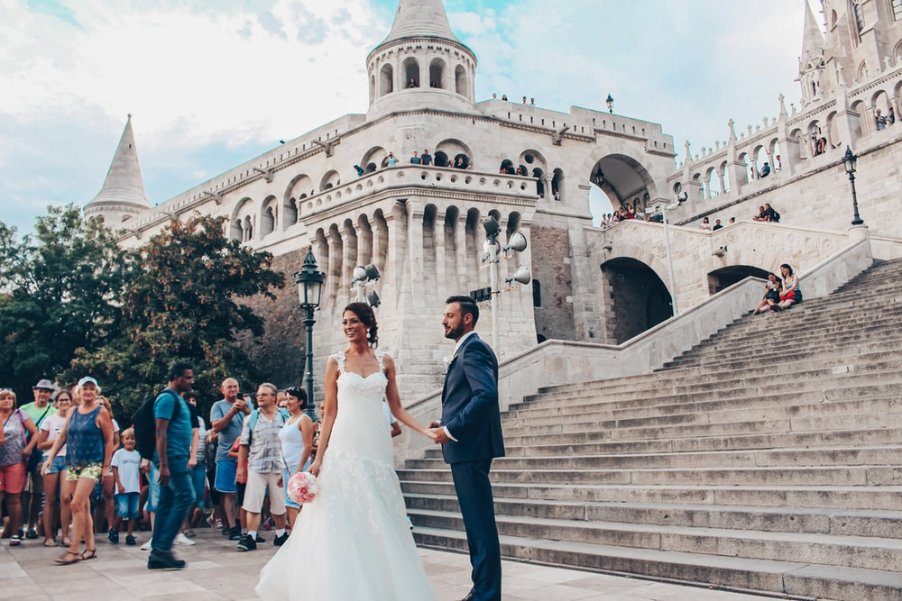 man in black suit jacket and woman in white wedding dress walking on stairs during daytime