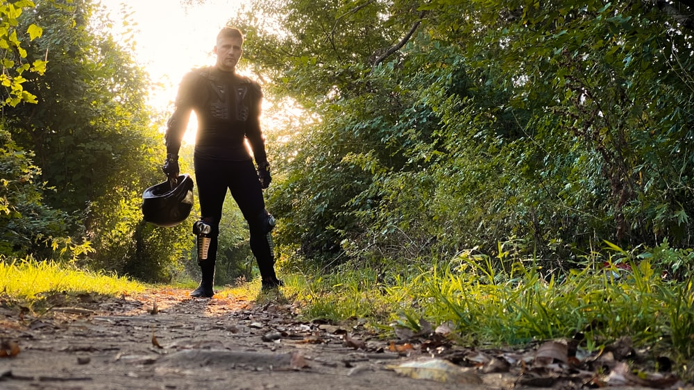 man in black pants carrying black backpack walking on dirt road during daytime