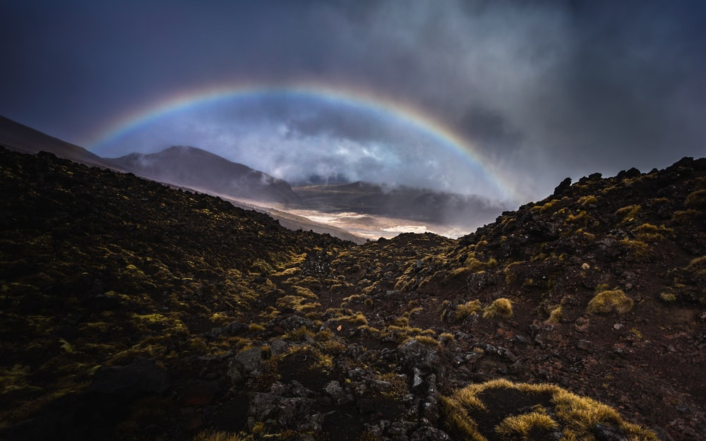 rainbow over brown and green mountain