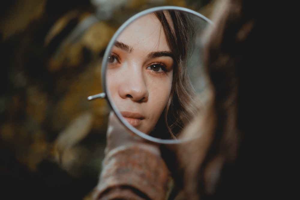 woman holding magnifying glass with brown liquid
