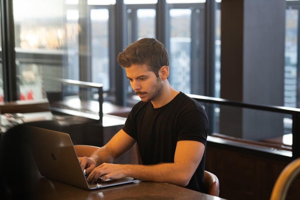 man in black crew neck t-shirt using macbook