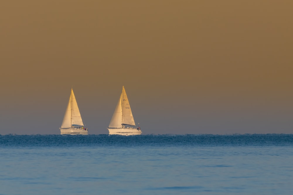 two white sail boats on brown sand during daytime