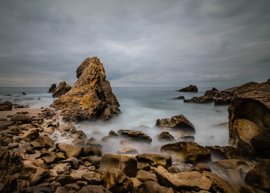 Brown Rock Formation On Sea Under White Clouds During Daytime - unsplash