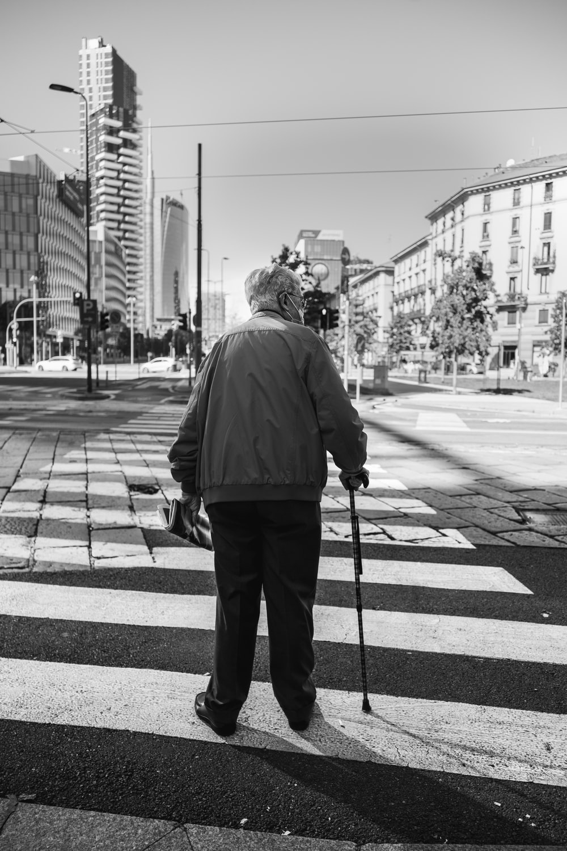 man in black jacket and pants standing on sidewalk during daytime