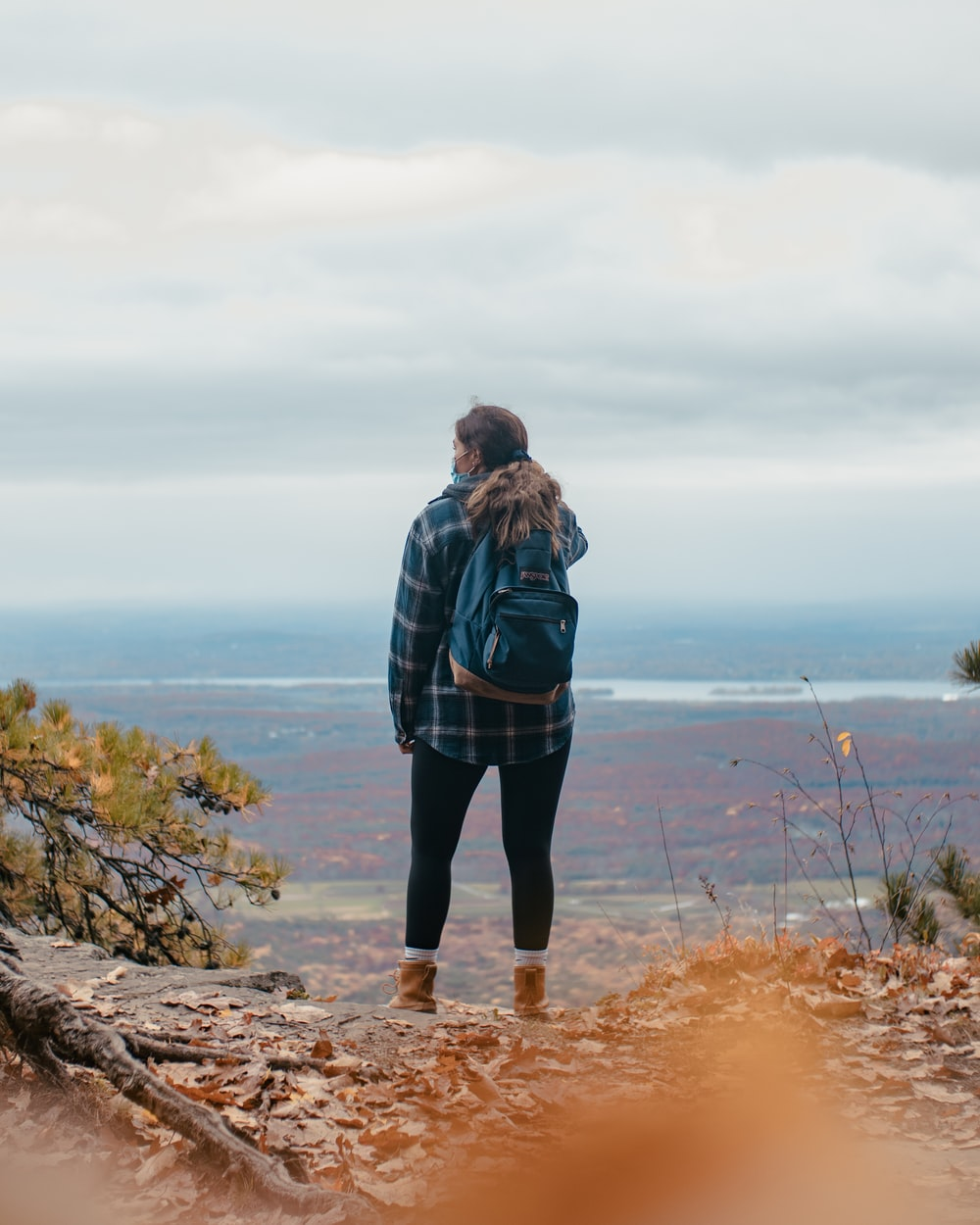 woman in black and gray plaid coat standing on rock formation near body of water during
