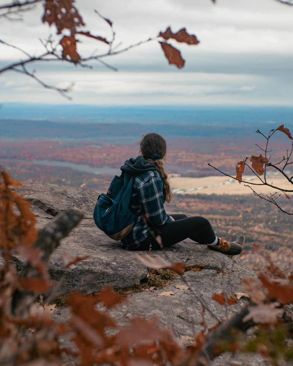 man in black jacket sitting on rock during daytime