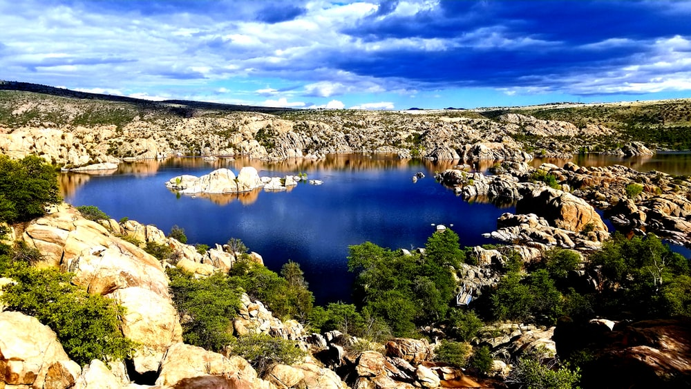 blue lake surrounded by brown rocks under blue sky during daytime