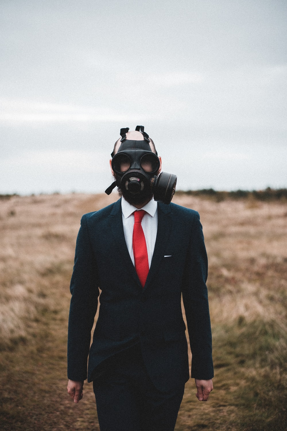 person in black suit wearing gas mask