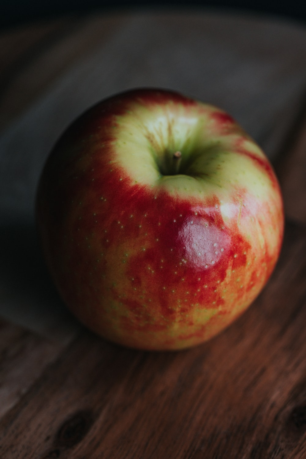 red apple fruit on brown wooden table
