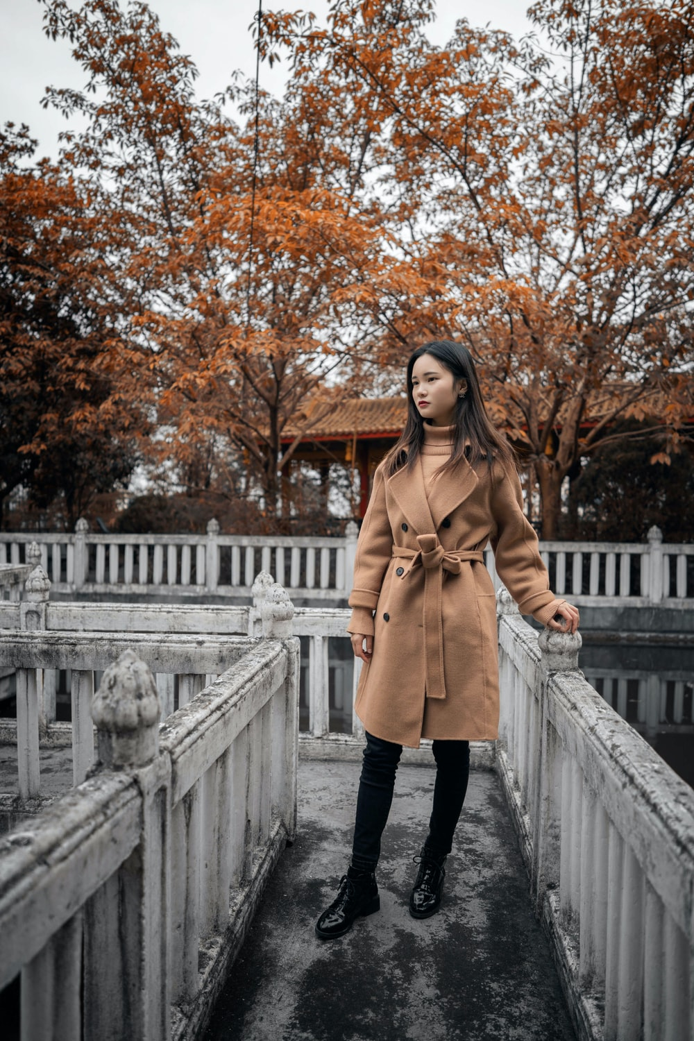 woman in brown coat standing on white bridge during daytime