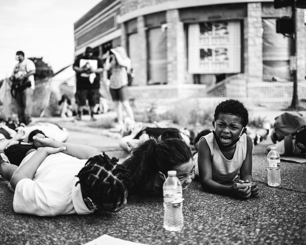 grayscale photo of man and woman sitting on ground