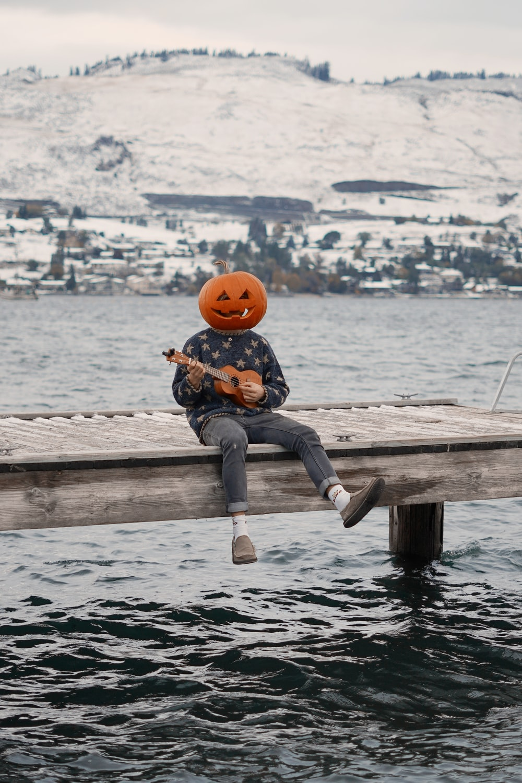 boy in blue denim jeans and orange helmet sitting on brown wooden dock during daytime