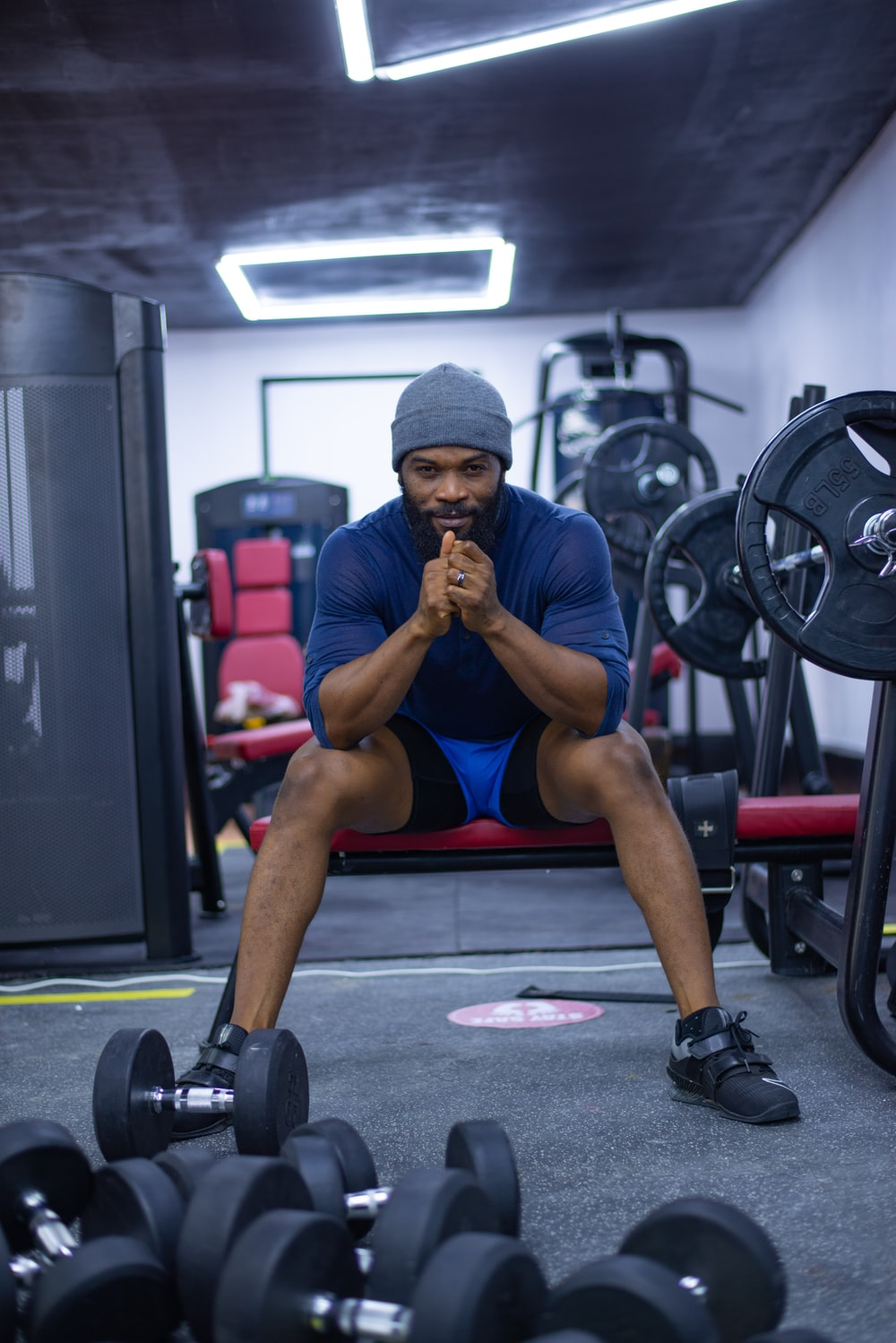 man in blue tank top and blue shorts sitting on black and red exercise equipment