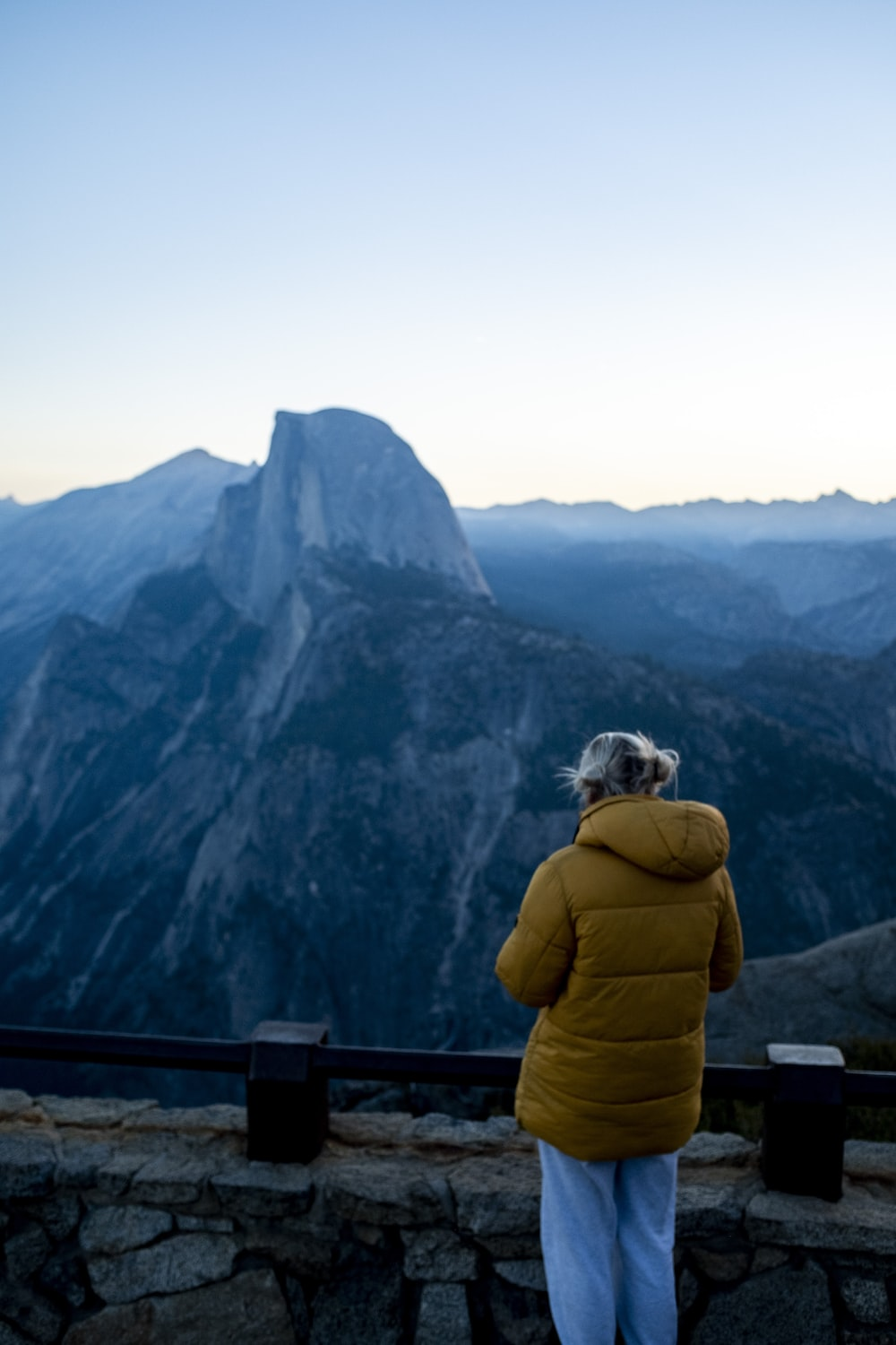 person in yellow jacket sitting on brown wooden fence looking at green mountains during daytime