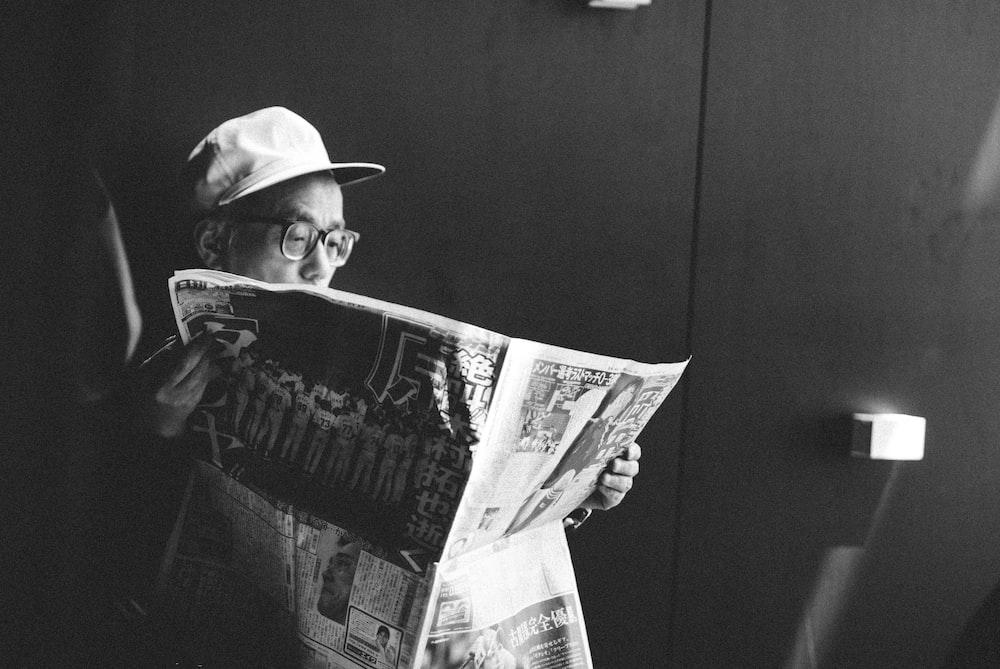 man in black shirt reading newspaper