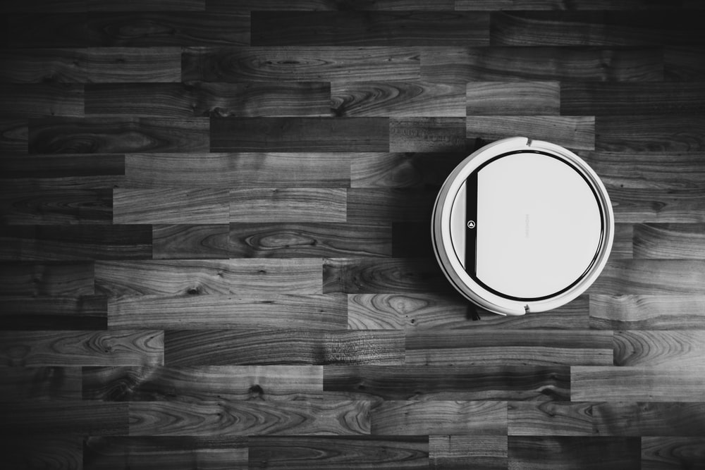 grayscale photo of round frame on wooden floor