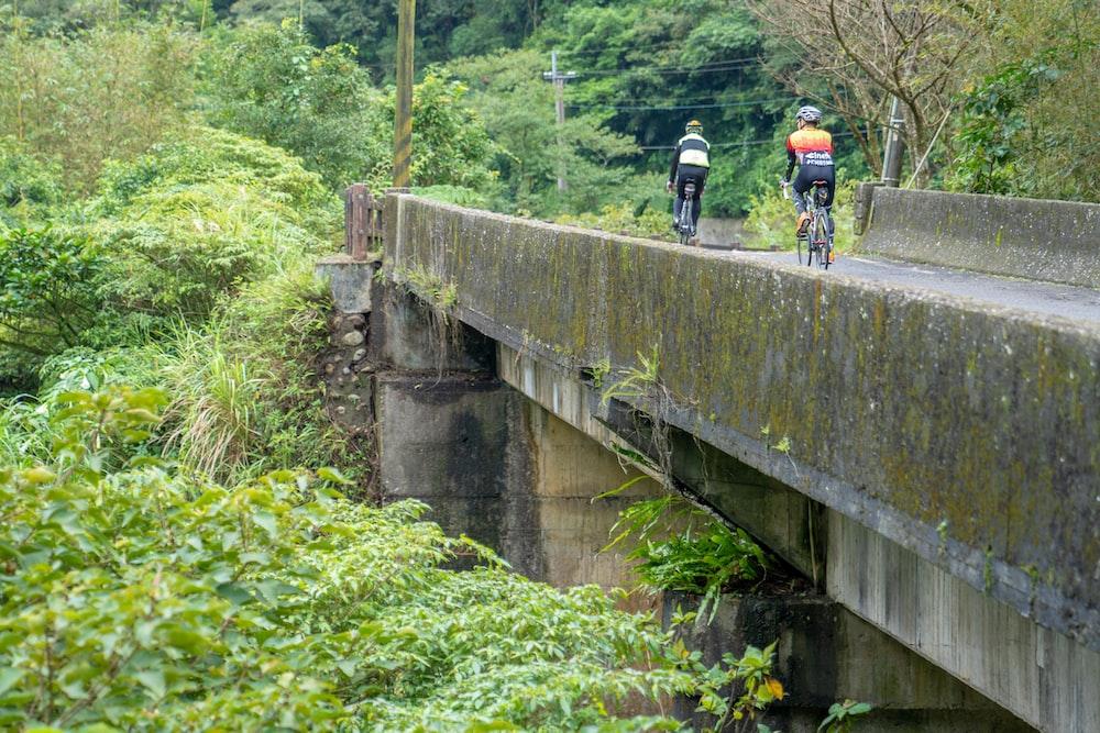 man in black shirt and black shorts riding bicycle on bridge during daytime