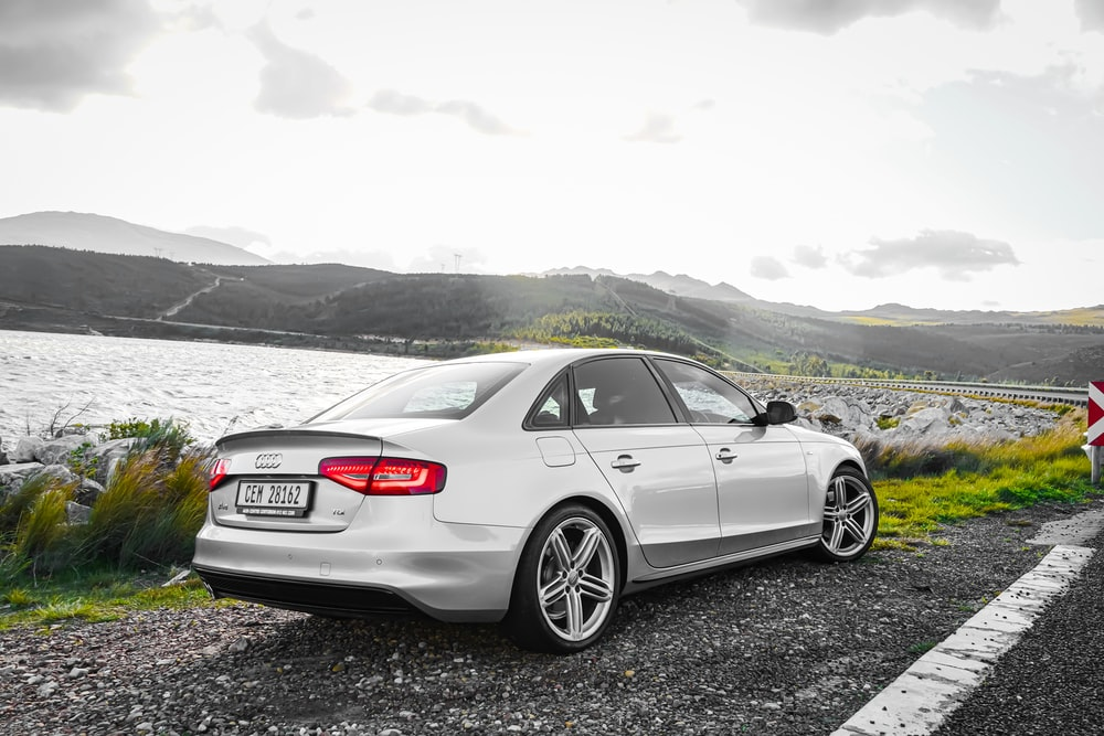 white bmw m 3 coupe on black soil near body of water during daytime