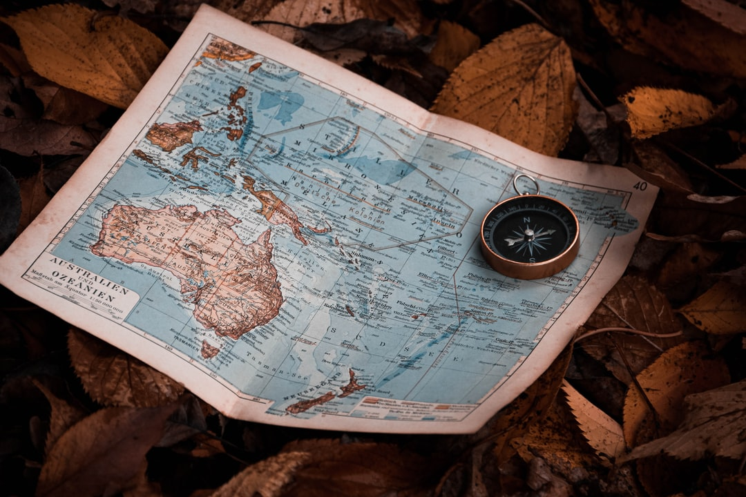 My Old Compass and A Map From Oceanie On A Bed of Leaves. - unsplash