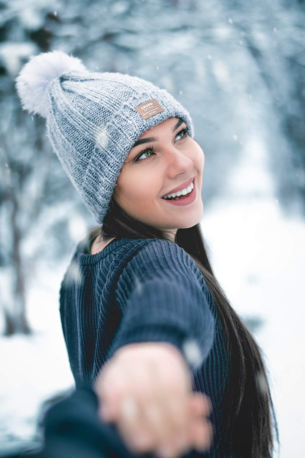 woman in blue knit cap and blue knit sweater smiling