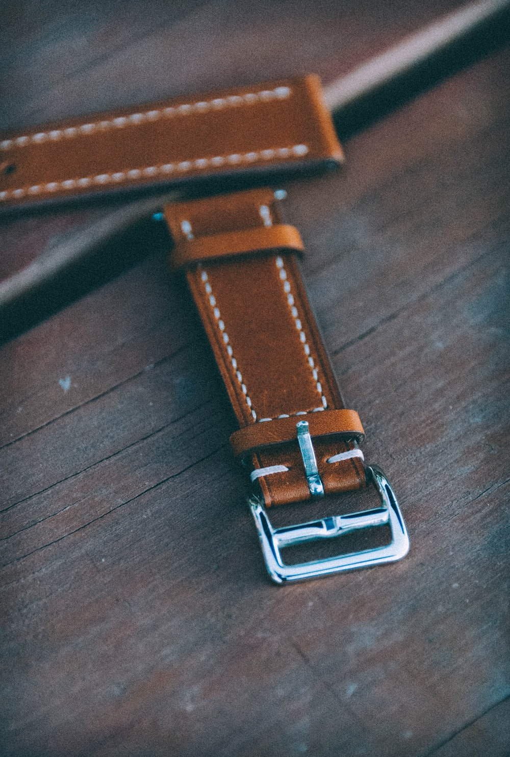 brown leather belt on brown wooden table
