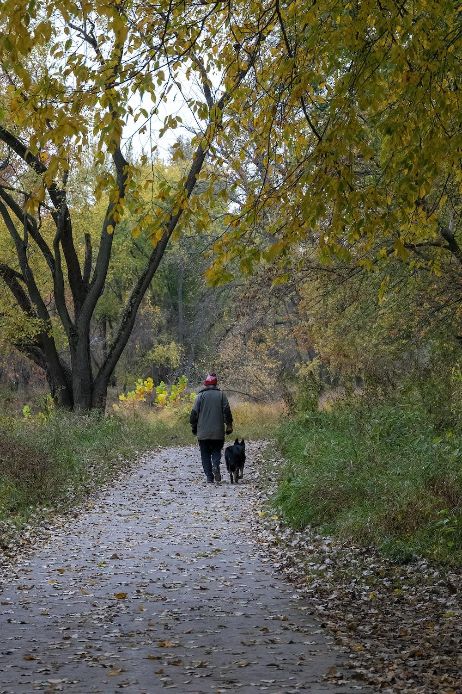 man in black jacket walking on pathway between trees during daytime