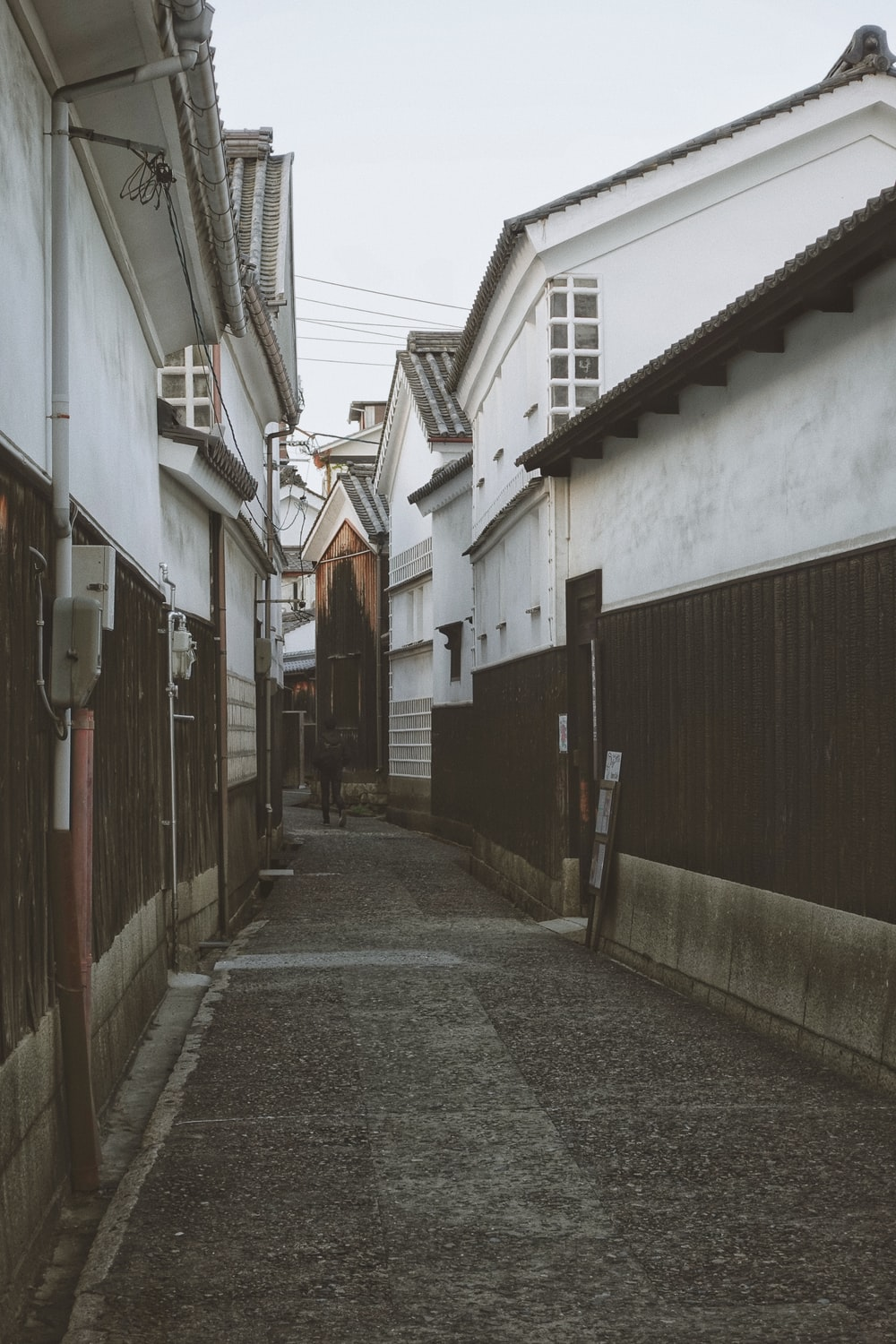 empty street between concrete houses during daytime