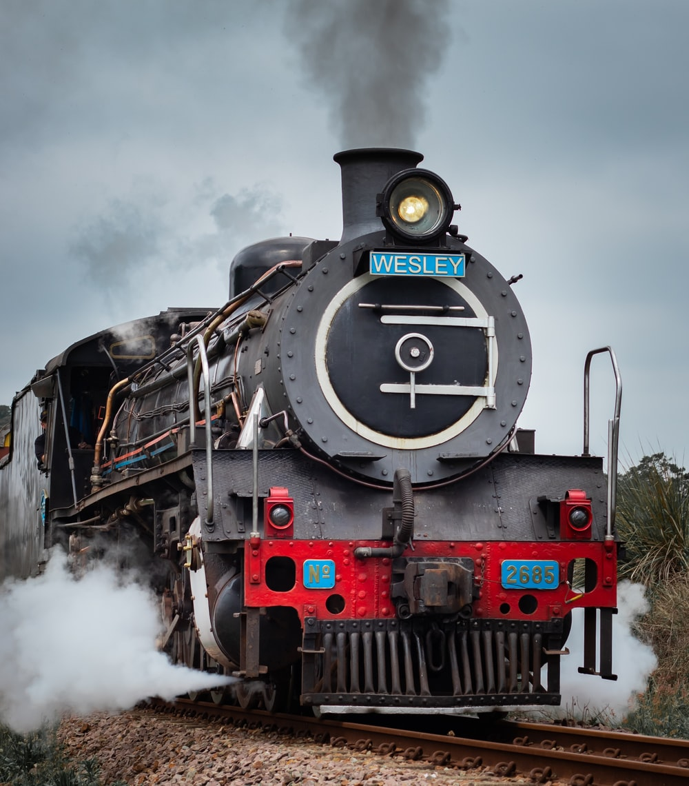 black and red train on rail tracks under cloudy sky during daytime