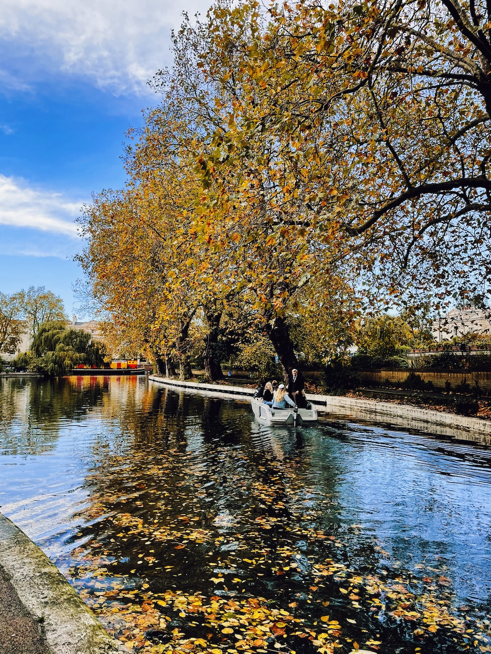 man and woman sitting on bench near river during daytime