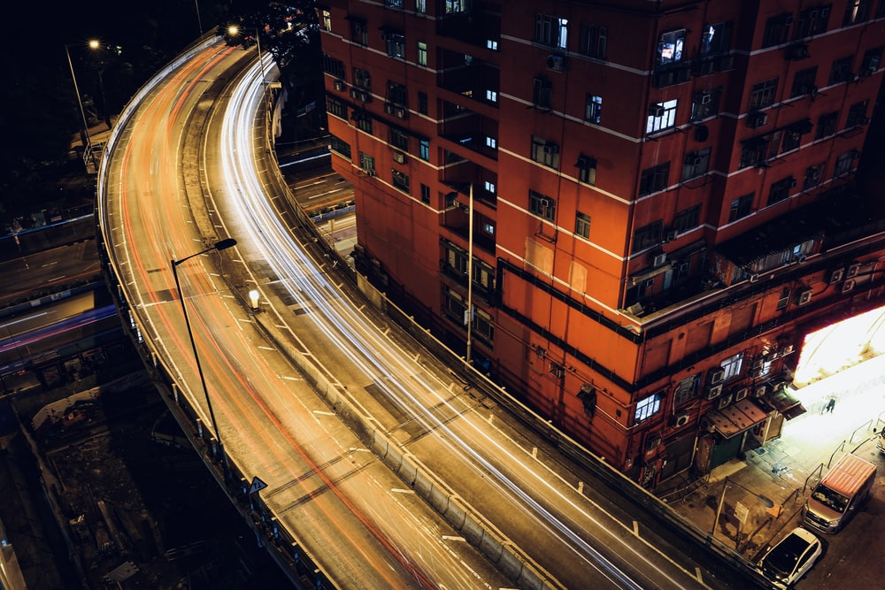 time lapse photography of cars on road near brown building during night time