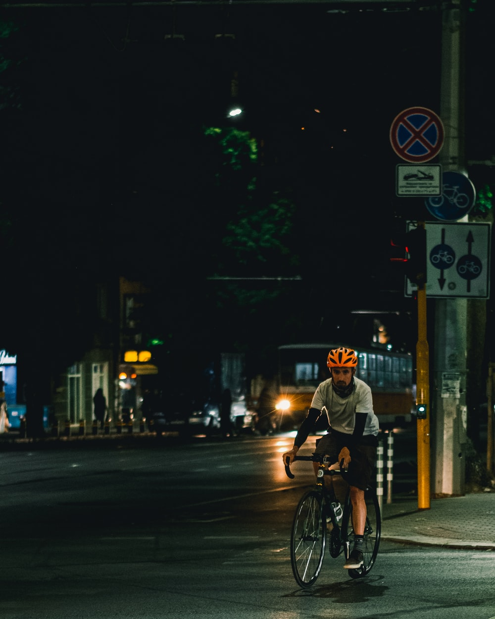 man in black jacket riding bicycle on road during night time