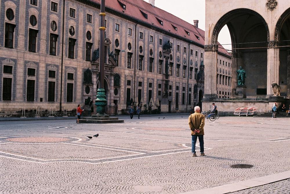 woman in yellow jacket walking on sidewalk during daytime