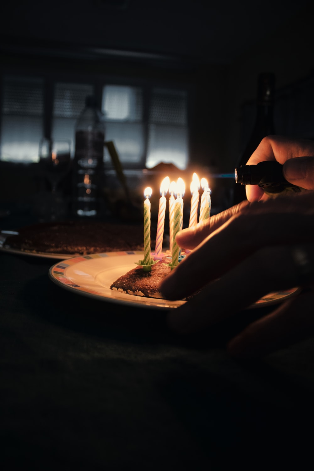 person holding lighted candles on white ceramic round plate