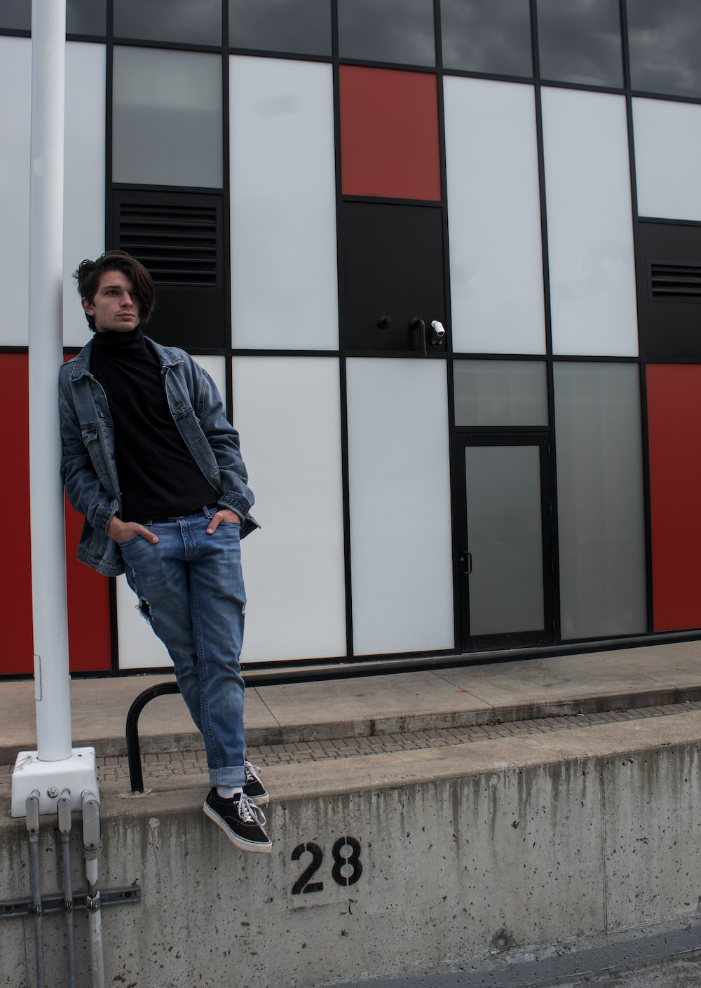 man in black jacket and blue denim jeans standing beside white and red building during daytime
