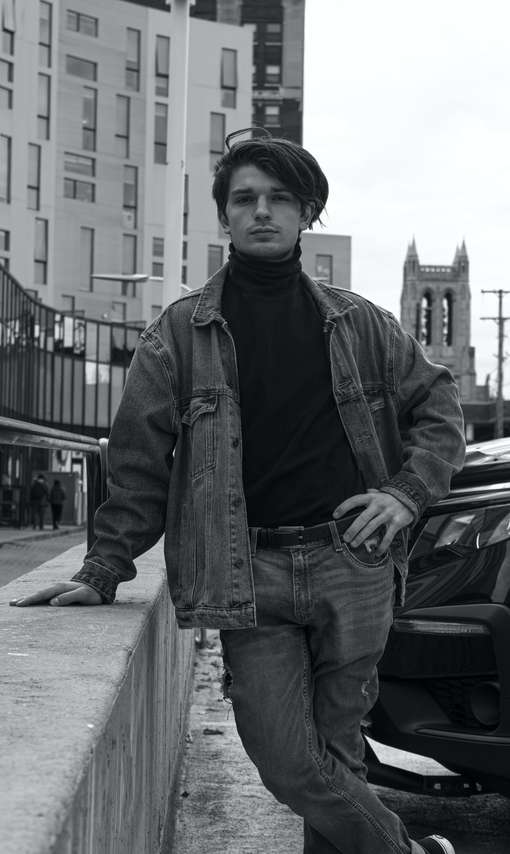 man in black leather jacket and denim jeans standing beside car