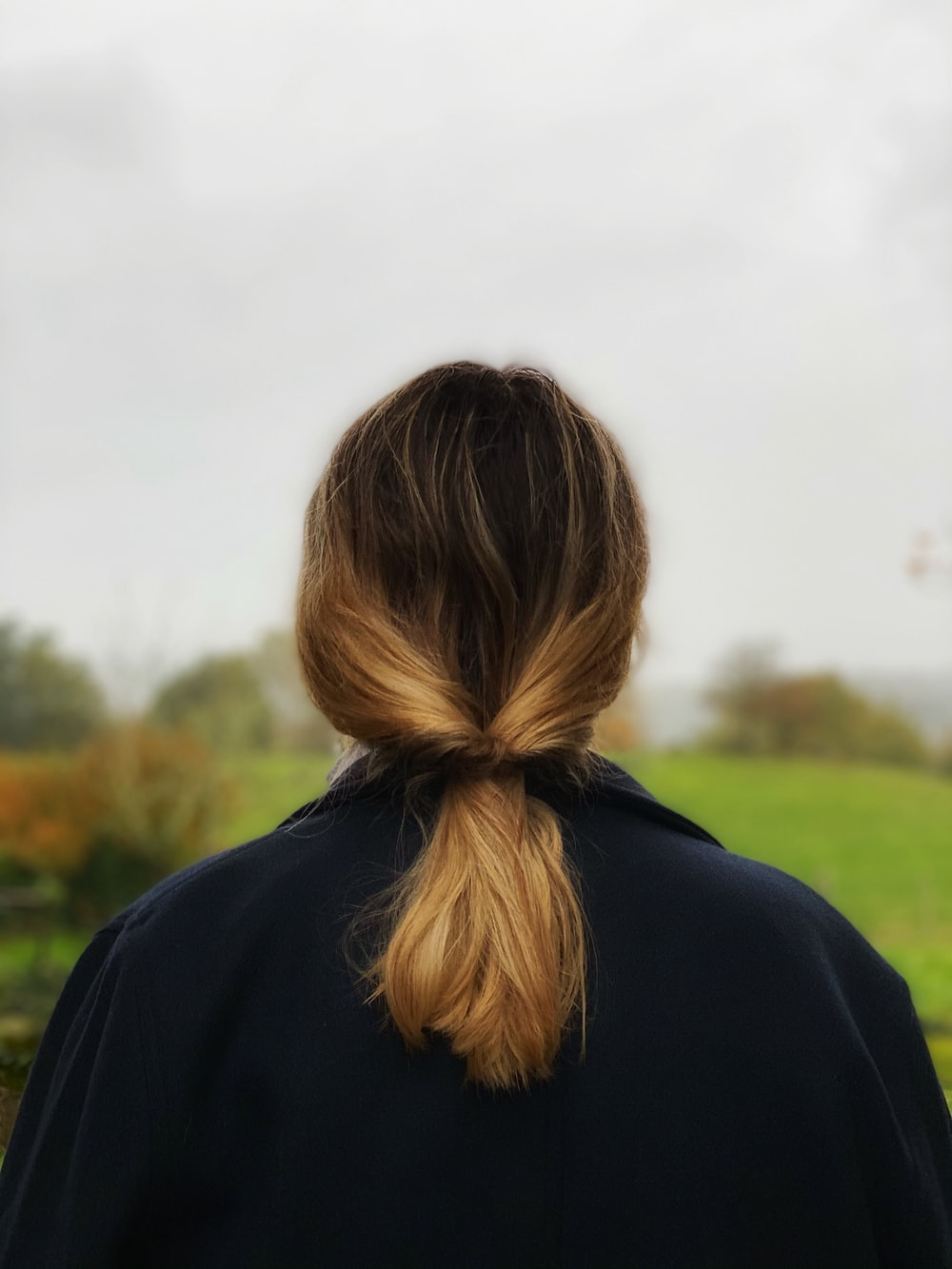 woman in black hoodie standing on green grass field during daytime