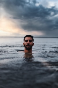 man in water under cloudy sky during daytime