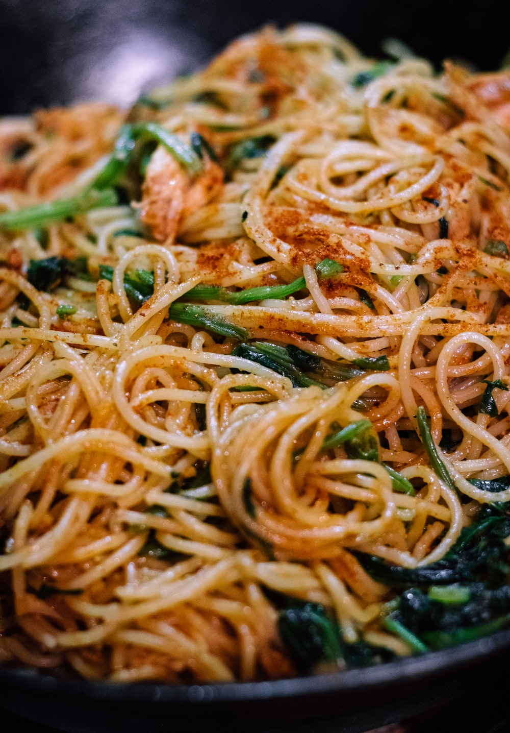 spaghetti with sauce on black plate