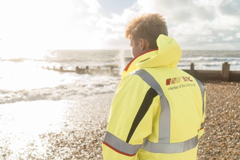 man in yellow and white jacket standing on beach during daytime