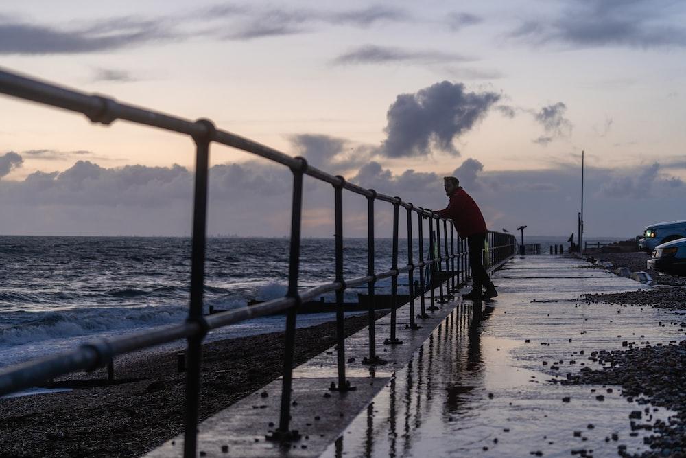 black metal railings on sea dock under white clouds during daytime